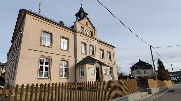 Ein alleinstehendes, braunes Altbauhaus mit zwei Etagen und Giebel, umgrenzt von einem Lattenzaun.