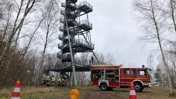 Ein Feuerwehrauto steht vor einem hohen Metallturm im Wald, Feuerwehrleute steigen hinauf.