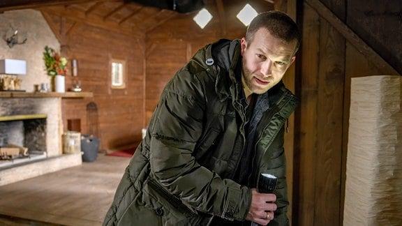 Tim (Florian Frowein) leuchtet in einem beleuchteten Raum sein Gesicht mit einer Taschenlampe an.
