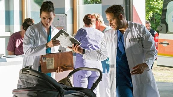 Während Tom Zondek (Tilman Pörzgen, l.) aus der russischen Patientenakte nicht schlau wird, erkennt Dr. Moreau (Mike Adler, r.) sofort, wie schlimm es um den kleinen Patienten Timofej steht.