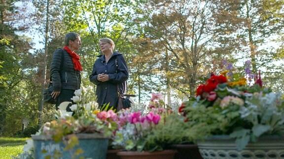 Insel Volkmann (li.) sucht sich mit Unterstützung einer Bestatterin eine passende Grabstelle für sich selbst auf dem Südfriedhof in Leipzig aus.