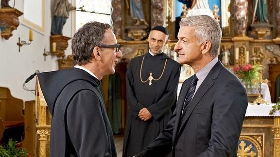 Pater Nikolaus (Roland Eugen Beiküfner, 2.v re.) wird Zeuge, als sich Bernhard Stolz (Dominick Raacke) und sein Bruder Hannes (Heio von Stetten, li.) nach langer Zeit wiedersehen.