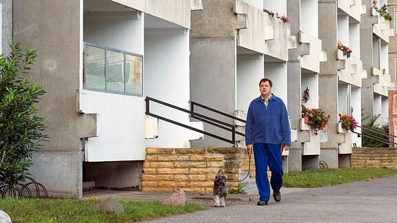 Roger (Charly Hübner) dreht mit seinem Hund eine Runde um den Plattenbau.