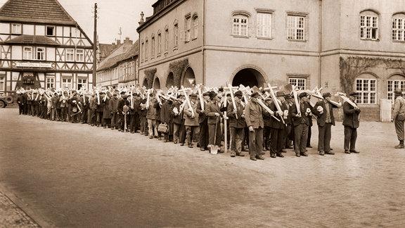 Die Einwohner Gardelegens ziehen mit Kreuzen aus der Stadt, um im April 1945 Gräber für die Opfer des Massakers anzulegen.