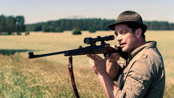 Ein Jäger (Ronald Zehrfeld) entdeckt einen Wolf und will ihn erschießen, er rennt weg.