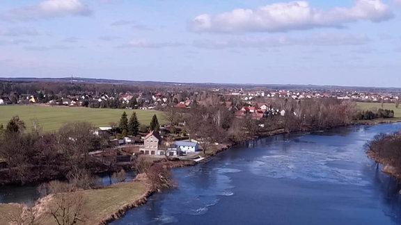 Ein Dorf erstreckt sich an einem Fluss entlang, dessen Ufer vereist sind.