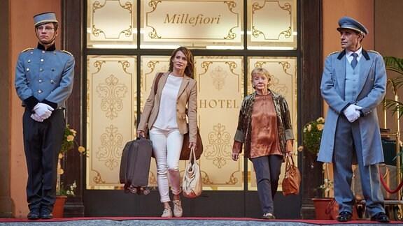 Andrea (Anja Kling, li.) und ihre Mutter Helga (Christine Schorn) vor einem Hotel mit Hotelportiers.