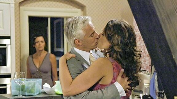 Petra (Angela Roy, im HG) beobachtet schockiert, wie ihr Mann Thomas (Gerry Hungbauer, M.), leidenschaftlich Tanjas beste Freundin Miriam (Sarah Maria Besgen, r.) küsst.