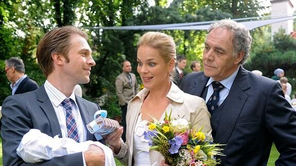 Helmuth (Christian Kohlund, rechts) und Laura (Angela Sandritter) stehen neben Jobst (Hubertus Grimm), der ein Kleikind im Arm hält.