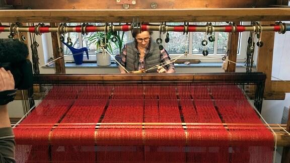Frau Schönfeldt stellt Theaterdekorationen an einem 100 Jahre alten Handwebstuhl her.