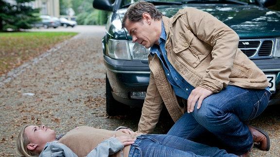 Sandra Schwartenbeck (Marie-Luise Schramm, liegend) hat sich mutig von das Auto von Thies Tönnesen gestellt und somit seine Flucht verhindert. Finn Kiesewetter (Sven Martinek, r.) ist froh, dass ihr nichts weiter passiert ist.