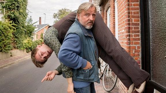 Ein Mann hat einen jungen Mann über seine Schulter gelegt.