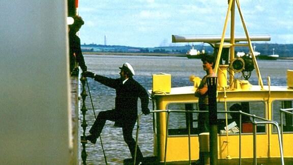 Der Außenlotse steigt über eine Leiter auf ein Schiff.