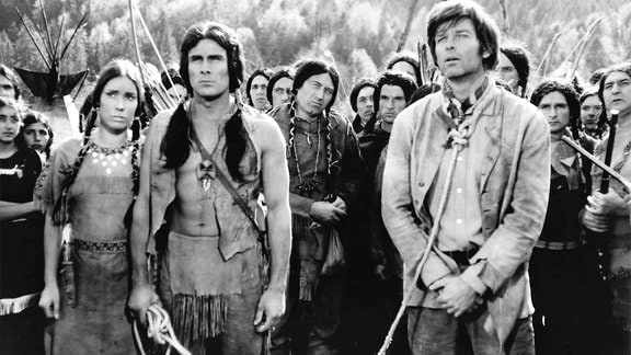 Ein Cowboy an einer Leine steht vor eine Gruppe Indigener, einer von diesen hält das Ende der Leine.