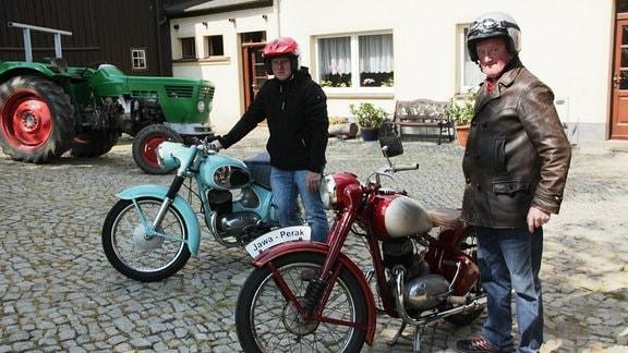 Zwei Männer stehen neben Mopeds.