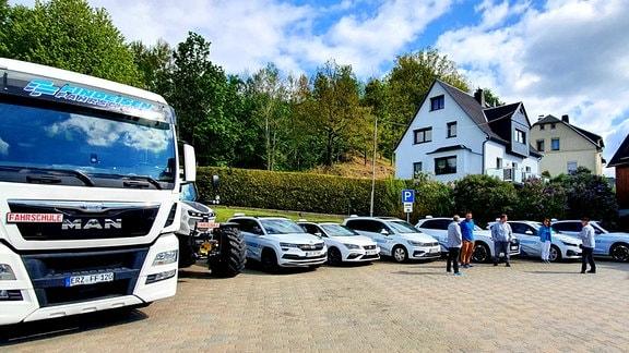 Mehrere Pkw und ein Lkw stehen auf einem Parkplatz vor einem Haus.