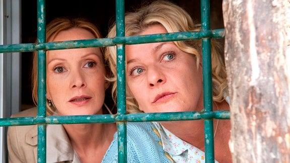 Lisbeth (Saskia Vester, rechts) und Carla (Katja Flint) blicken durch ein vergittertes Fenster.