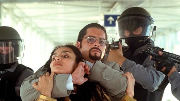 Karl Hrulitschka (Fritz Karl) nimmt  seine eigene Freundin Maria Vasquez (Christina Contes) als Geisel. Drei Angehörige eines SEK stehen um sie herum.
