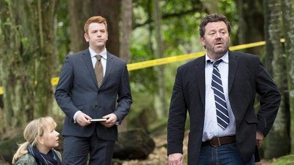 Detective Shepherd (Neill Rea, re.), Kristin Sims (Fern Sutherland, li.) und Breen (Nic Simpson) übernehmen die Ermittlungen. Auf dem Waldboden liegt die Leiche von Hayden (Francis Mountjoy).