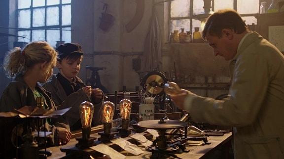 Thomas Alva Edison (Florian Lukas) erklärt Juna (Claire Wegener) und Hugo (Yuri Gayed), wie der Bau einer Glühbirne funktioniert.