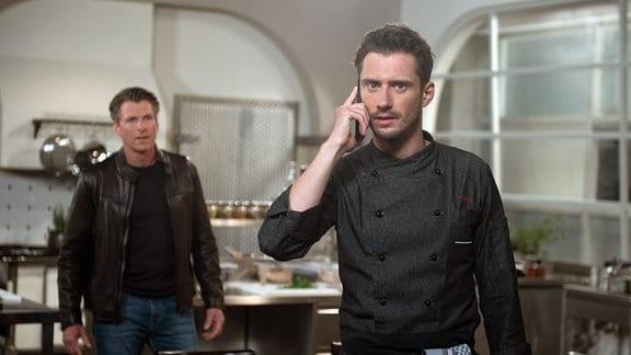 Henning (Herbert Ulrich, l.) hört mit, als Alex (Philipp Oliver Baumgarten, r.) die Nachricht erreicht, dass Judith Oskar ohne Absprache aus der Kita geholt hat.