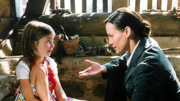 Sarah (Sonja Kirchberger, re.) und Marie (Sina Richardt) sitzen sich gegenüber; sie blicken sich an.
