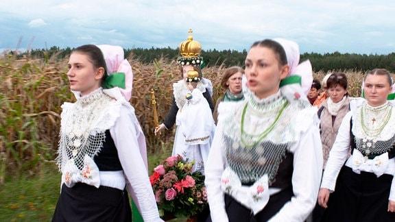 Junge Sorbinnen in Tracht tragen die festlich geschmückte Marienstatue nach Rosenthal.