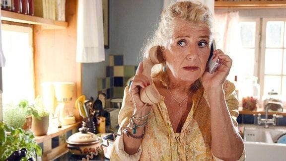 Fanny (Jutta Speidel) telefoniert und hält sich das linke Ohr zu.