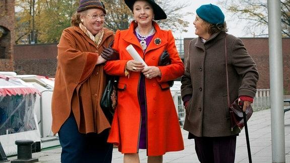 Kiesewetters Tanten Ria (Ulrike Bliefert, l.) und Toni (Petra Kelling, r.) mit Marie Guteson (Annelinde Gerstl, M.), auf einer Straße.
