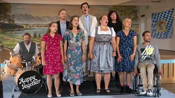 Mirkos Chor singt beim Wettbewerb (v. l. n. r.): Rainer (David Baalcke), Nele (Aleen Jana Kötter), Georg (Matthias Lier), Elena (Marie Leuenberger), Goran (René Geisler), Elke (Barbara Bauer), Mirkos Mutter (Gundi Ellert), Rosa (Eva Herzig) und Felix (Tom Gronau).