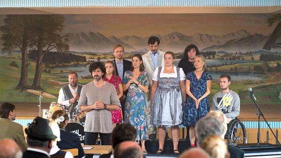 Mirkos (Pasquale Aleardi, 2. v. li.) Chor möchte singt beim Wettbewerb (v. l. n. r.): Rainer (David Baalcke), Nele (Aleen Jana Kötter), Georg (Matthias Lier), Elena (Marie Leuenberger), Goran (René Geisler), Elke (Barbara Bauer), Mirkos Mutter (Gundi Ellert), Rosa (Eva Herzig) und Felix (Tom Gronau).