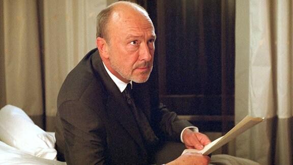 Josef Lieblich (Marcel Herz-Kestranek) hört im Hotelzimmer aufmerksam seiner Frau Maria Lieblich zu.