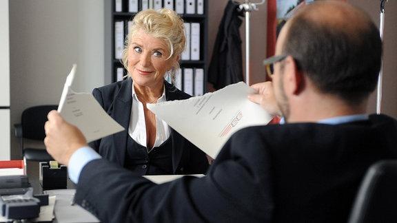 Fanny Steininger (Jutta Speidel) sitzt einem Herren mit Halbglatze gegenüber. Wr hält Papiere in der Hand.