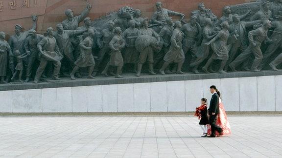 """Sin Mi und ihre Eltern legen am Denkmal des """"Großen Führers"""" feierlich Blumen nieder."""