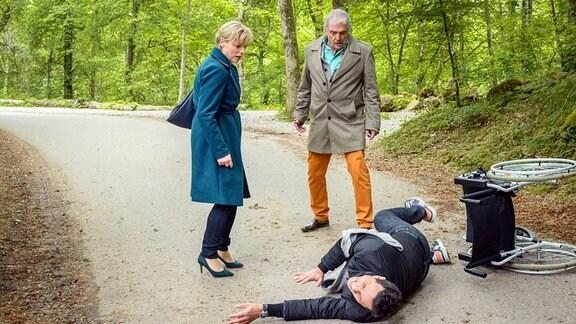 Linda (Julia Grimpe, l.) und André (Joachim Lätsch, M.) stehen auf einem Waldweg. Vor ihnen liegt Dirk (Markus Pfeiffer, r.) neben einem umgekippten Rollstuhl.