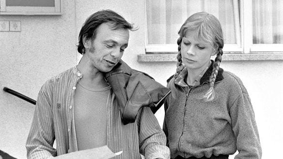 Jürgen Langer (Dieter Bellmann) steht neben seiner Schwester Petra (Karin Düwel) und blickt auf Papiere.