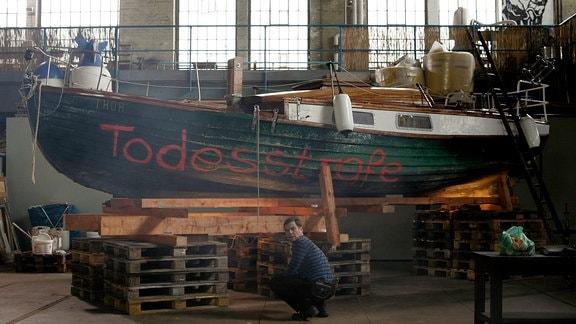 """Im Veranstaltungszentrum """"Fabrik"""" hat Hans Freytag (Tom Quaas) mit Jugendlichen des Viertels ein altes Segelboot restauriert. Der Mörder hat """"Todesstrafe""""an den Rumpf gesprüht."""
