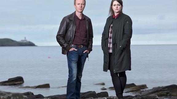 Tosh (Alison O'Donnell) und ihr Kollege Sandy (Steven Robertson) vor einem Gewässer.