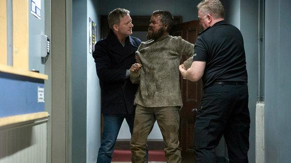Shetland-Ermittler Jimmy Perez (Douglas Henshall) hält mit einem Kollegen den Hauptverdächtigen Thomas Malone (Stephen Walters) fest.