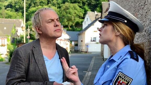 Kati (Diana Amft - in Uniform) und Killmer (Uwe Ochsenknecht - in Zivil) hat einem dörflichen Ambiente - im Dialog.