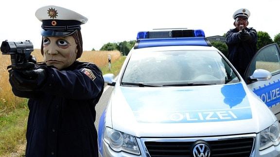 Zwei Personen mit Masken (satirische Darstellung der Bundeskanzlerin Merkel und des Ex-US-Präsidenten Obama9 in Polizeiuniformstehen neben einem Streifenwagen. Beide Personen haben jeweils eine Pistole in den Händen.