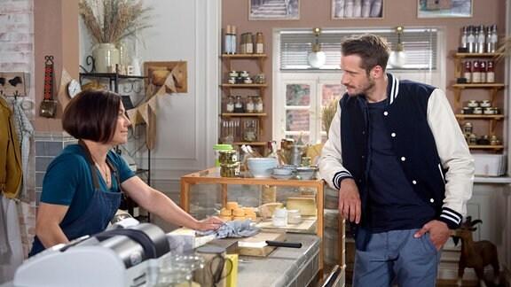 Astrid (Claudia Schmutzler, l.) steht hinter einer Kuchentheke; Alex (Philipp Oliver Baumgarten, r.) davor.