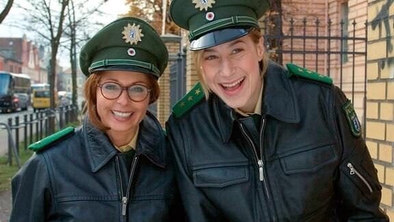 Julia (Christina Plate, li.) und ihre Kollegin Teresa (Helene Grass) haben sich als Polizistinnen verkleide. Sie lächeln in die Kamera.
