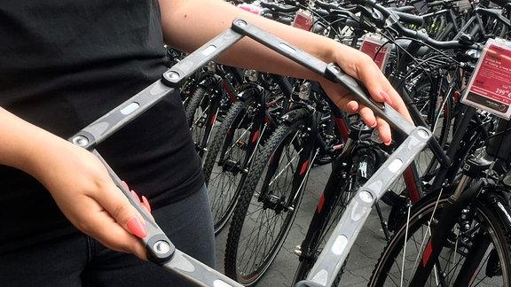 Eine nicht erkennbare Person hält ein Fahrradschloss in den Händen.