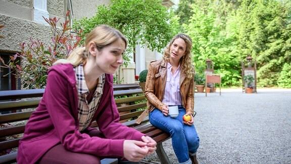 Franzi (Léa Wegmann, r.) und Amelie (Julia Gruber, l. sitzen auf einer Gartenbank im Freien. Sie sprechen miteinander.