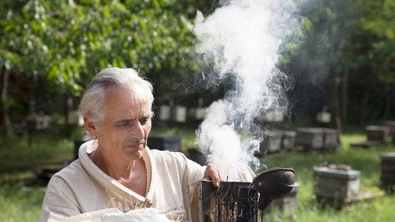 Imker Patrick Genau kündigt sich mit Rauch bei den Bienen an.