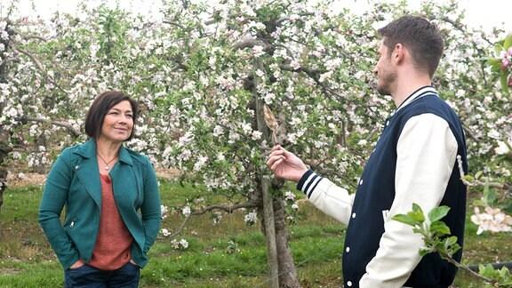 Alex (Philipp Oliver Baumgarten, r.) und Astrid (Claudia Schmutzler, l.) stehen sich in einem blühenden Obstgarten gegenüber.