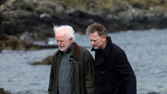 Shetland-Ermittler Jimmy Perez (Douglas Henshall, re.) misstraut seinem Vorgänger Drew McColl (Sean McGinley). Sie laufen gemeisam durch das Brackwasser.
