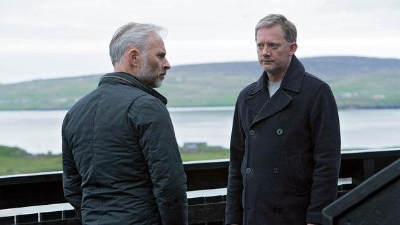 Perez (Douglas Henshall) und Duncan (Mark Bonnar, li.) stehen sich gegenüber. Ihre Blicke treffen sich nicht.