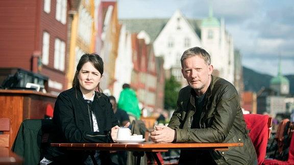 Perez (Douglas Henshall) und Tosh (Alison O'Donnell) sitzen an einem Tisch im Freien. Im Hintergrund eine Straße mit Giebelhäusern.